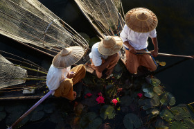 Fishermen take a break to admire a beautiful lotus flower at Inle lake