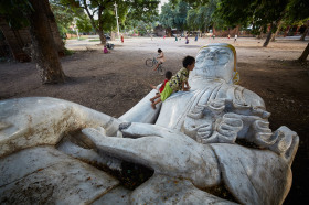 Kids playing around a fallen statue of Buddha