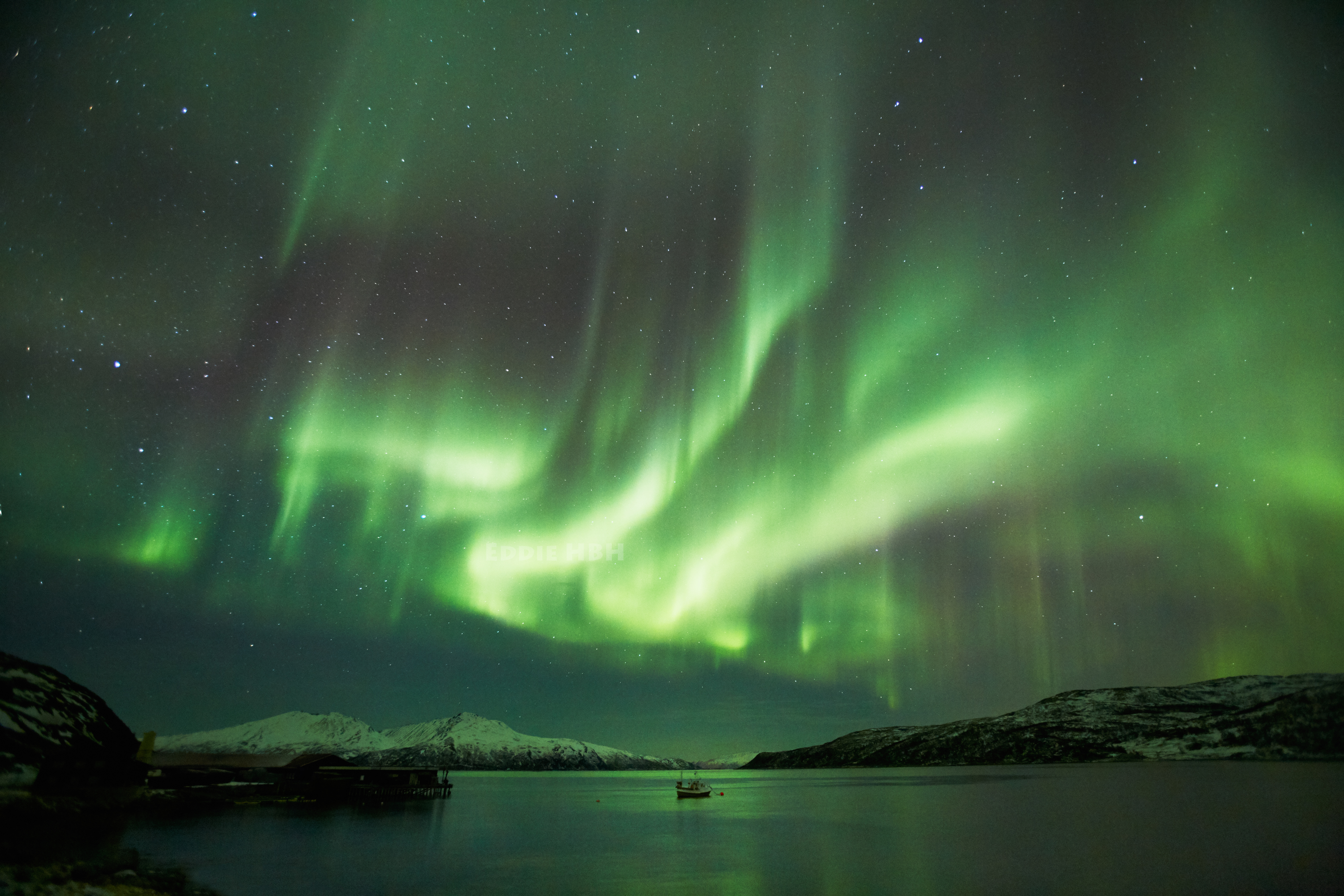 Lonely boat in the middle of a show of Northern Lights