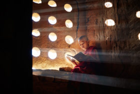 Young monk reading in a temple in Bagan